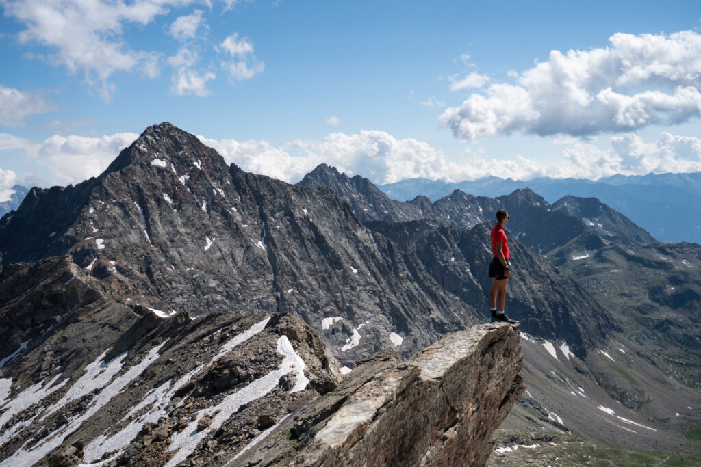 A man standing on a mountain ridge in Italy